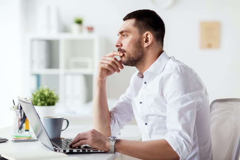 businessman with laptop computer thinking at the office. Helping manage IT clients in Alberta.