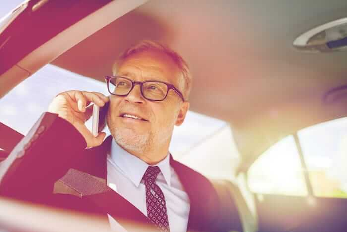Older man talking on his phone in the car to his IT clients in Alberta.